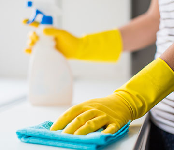 Woman cleaning countertop with rag and spray bottle